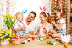 复活节快乐!家庭母亲、父亲和孩子绘鸡蛋为 免版税库存照片