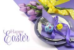复活节快乐黄色和紫色淡紫色淡紫色题材复活节桌餐位餐具 库存图片