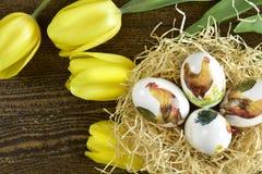 复活节手在decoupage样式的绘画鸡蛋 免版税库存图片