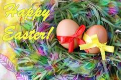 复活节手工制造装饰的贺卡:与鞋带丝带的两个黄色鸡蛋在绿草枝杈在黄色背景筑巢 免版税图库摄影