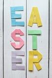 复活节折叠了纸在白色木板条土气背景的origami五颜六色的字法 免版税库存照片