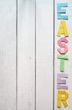 复活节折叠了纸在白色木板条土气背景的origami五颜六色的字法 库存照片