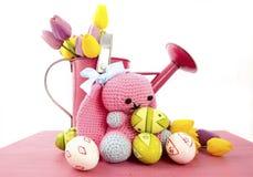 复活节春天题材桃红色喷壶用复活节彩蛋和手工制造钩针编织编织羊毛兔宝宝 免版税库存照片