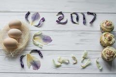 复活节构成用鸡蛋和花的干紫罗兰色瓣 题字2017年 免版税库存照片
