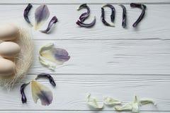 复活节构成用鸡蛋和花的干紫罗兰色瓣 题字2017年 图库摄影