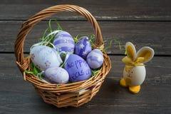 复活节柳条筐用色的鸡蛋和一只小蛋兔子在灰色木板 免版税库存图片
