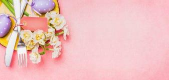 复活节桌与春天花、装饰鸡蛋和利器的餐位餐具在浅粉红色的背景,顶视图 免版税库存照片