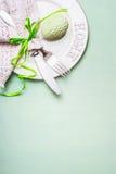 复活节桌与用有花边的餐巾装饰的板材、利器和鸡蛋的餐位餐具在浅绿色的背景,顶视图 库存图片