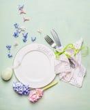 复活节桌与空白的板材,风信花的餐位餐具开花在浅绿色的背景,顶面v的装饰、利器和装饰鸡蛋 免版税图库摄影