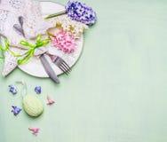 复活节桌与花和鸡蛋的餐位餐具在浅绿色的背景,顶视图 免版税图库摄影
