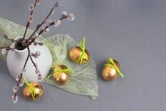 复活节概念、金黄鸡蛋和褪色柳分支,在石英厨房上面的白色花瓶 免版税库存图片