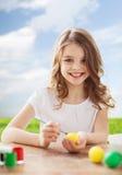 复活节的微笑的小女孩着色鸡蛋 库存图片