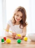 复活节的微笑的小女孩着色鸡蛋 免版税库存照片