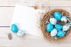 复活节背景用在巢和问候的蓝色和白鸡蛋 库存图片