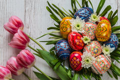复活节背景用复活节彩蛋和桃红色郁金香在轻的木背景 以巢的形式花的布置 库存图片