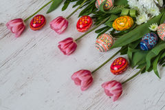 复活节背景用复活节彩蛋和桃红色郁金香在轻的木背景 库存图片