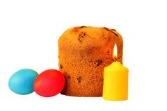 复活节蛋糕、假日多彩多姿的鸡蛋和一个灼烧的蜡烛 库存照片