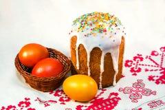复活节蛋糕和被绘的鸡蛋在一块毛巾与刺绣 库存图片