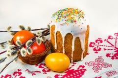 复活节蛋糕和被绘的鸡蛋在一块毛巾与刺绣 免版税库存照片