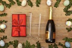 复活节装饰、礼物、champagner bootle和香槟玻璃在木头 免版税库存图片