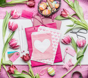 复活节装饰做 复活节工作区用鸡蛋、郁金香花和桃红色纸袋和信封与心脏,顶视图 免版税库存图片