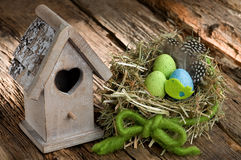 复活节装饰用五颜六色的鸡蛋和小鸟舍 免版税图库摄影