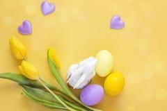 复活节装饰用复活节彩蛋、兔子和黄色郁金香 免版税库存照片
