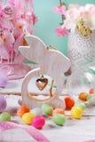 复活节装饰用木兔子和糖果鸡蛋 免版税库存图片