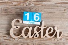 复活节雕刻了与立方体日历4月16日的木题字 背景上色节假日红色黄色 天16月 库存图片