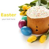 复活节面包、五颜六色的鸡蛋和黄色郁金香在白色背景(与样品文本) 免版税库存图片
