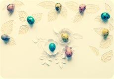 复活节颜色在白色背景的鹌鹑蛋,叶子从p切开了 库存图片