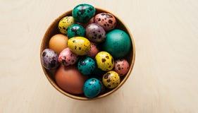 复活节 在一个木碗的五颜六色的鸡蛋在木背景 图库摄影