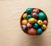 复活节 在一个木碗的五颜六色的鸡蛋 库存图片