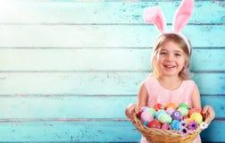 复活节-小女孩用篮子鸡蛋和兔宝宝耳朵 免版税库存图片