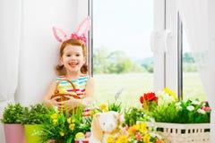 复活节 有兔宝宝耳朵和五颜六色的蛋sitti的愉快的儿童女孩 免版税图库摄影