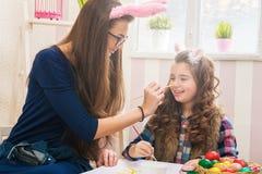 复活节-母亲和女儿油漆鸡蛋,在他们的兔宝宝耳朵 免版税库存图片