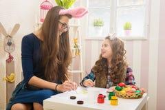 复活节-母亲和女儿油漆鸡蛋,在他们的兔宝宝耳朵 图库摄影