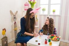 复活节-母亲和女儿油漆鸡蛋,在他们的兔宝宝耳朵 免版税库存照片