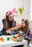 复活节-母亲和女儿油漆鸡蛋,在他们的兔宝宝耳朵 库存照片