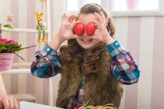 复活节-母亲和女儿滑稽的眼睛比鸡蛋 免版税库存照片