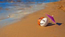 复活节滑稽的鸡蛋在海滩的伞下 库存照片