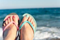 夏令时享受!夫人在海滩的` s脚 海浪 免版税库存照片