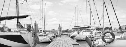 夏令时假期旅途冒险概念 花费他的时间的帅哥走在有观光的小游艇船坞上在期间 免版税图库摄影