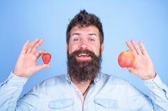 夏令时好处 人有胡子微笑拿着苹果和草莓在手蓝色背景中 果子和莓果在手上 库存图片