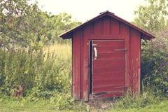 夏令时流洒的可爱的小红色 美丽的夏季具体照片 小屋/客舱/与深绿色一起流洒了 库存图片