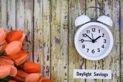 夏令时计时春天概念上面下来用白色时钟和橙色郁金香观看 免版税库存照片