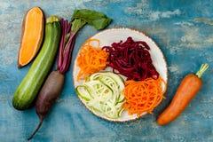 夏南瓜、红萝卜、白薯和甜菜根面条在板材 顶视图,顶上 蓝色土气背景 库存照片