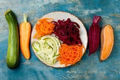 夏南瓜、红萝卜、白薯和甜菜根面条在板材 顶视图,顶上 蓝色土气背景 免版税库存照片