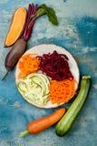 夏南瓜、红萝卜、白薯和甜菜根面条在板材 顶视图,顶上 蓝色土气背景 库存图片
