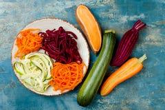 夏南瓜、红萝卜、白薯和甜菜根面条在板材 顶视图,顶上 蓝色土气背景 免版税图库摄影